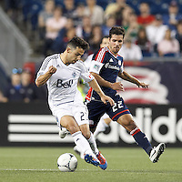 Vancouver Whitecaps FC midfielder Davide Chiumiento (20) dribbles as New England Revolution forward Benny Feilhaber (22) defends. In a Major League Soccer (MLS) match, the New England Revolution defeated Vancouver Whitecaps FC, 4-1, at Gillette Stadium on May 12, 2012.