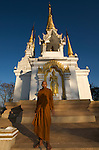 The Abbot of Wat Phratat (phra that) Doi Mae Aep, stood in front of his hilltop shrine. The shrine looks down onto the Mae Kok river valley in Chiang Rai, Thailand.