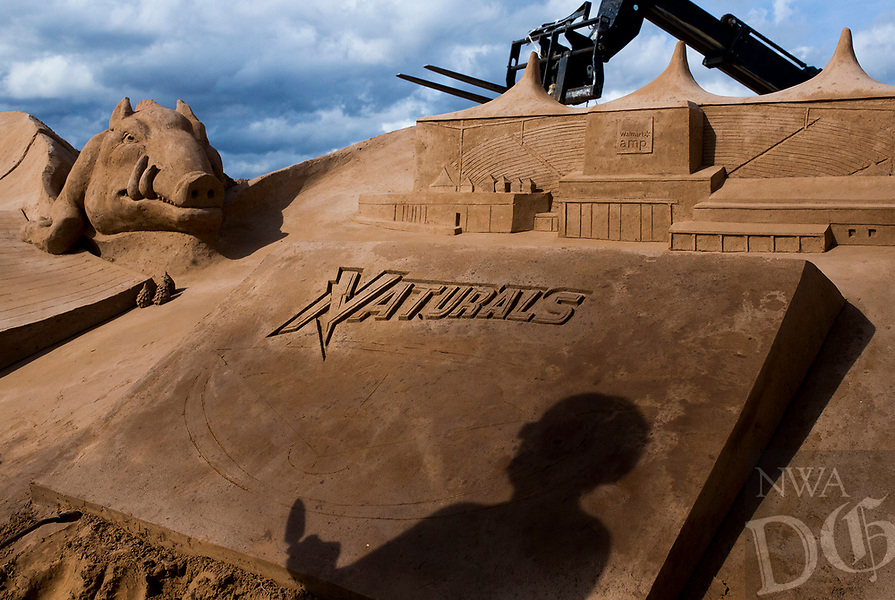 NWA Democrat-Gazette/CHARLIE KAIJO Artist Edith van de Wetering's shadow is shown on a sand sculpture she is building on Saturday, October 21, 2017 at Sullivan Square in Bentonville. Four artists started the sand project on Monday that will involved about 275 hours of building time and 280 tons of sand.