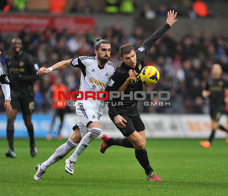 Swansea City's Chico battles hard for the ball with Manchester City's Edin Džeko -  01/01/2014 - SPORT - FOOTBALL - Liberty Stadium - Swansea - Swansea City v Manchester City - Barclays Premier League<br /> Foto nph / Meredith<br /> <br /> ***** OUT OF UK *****