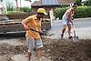 Women shovelling soil into lorry