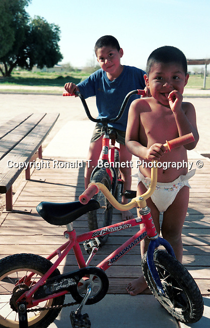 Indian boys play with bicycles, boys with bicycles, Native American boys, Native Americans, boys play, bicycle, indian children, Arizona, State of Arizona, Southwest, desert, 48th State, Last of contiguous states, Phoenix, Scottsdale, Grand Canyon, Indian reservations, four corners, desert landscape, exrophyte, western United States, Southwest, Mountains, plateaus, ponderosa pines, Colorado River,  Mountain lion, Navajo Nation, Indian children, Indian boys, Native American, Native American boys, boys play, boys with bikes, bikes, little boys with bicycles, bicycle, No daylight savings time, Arizona Territory, Arizona, AR, Fine Art Photography by Ron Bennett, Fine Art, Fine Art photography, Art Photography, Copyright RonBennettPhotography.com ©