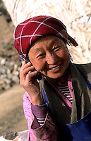 Elderly woman on cell phone in rural Tibet China