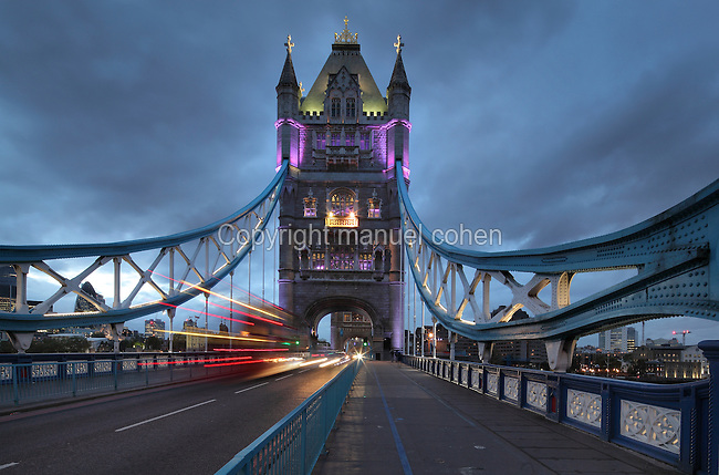 Traffic on Tower Bridge at night looking North, built 1886-94, next to the Tower of London on the river Thames, linking the boroughs of Southwark and Tower Hamlets, London, England. The bridge is both suspension bridge and bascule bridge, with the lower section rising using hydraulic motors to allow for the passing of boats. It is 244m long with 2 65m towers built on piers in the river. Picture by Manuel Cohen