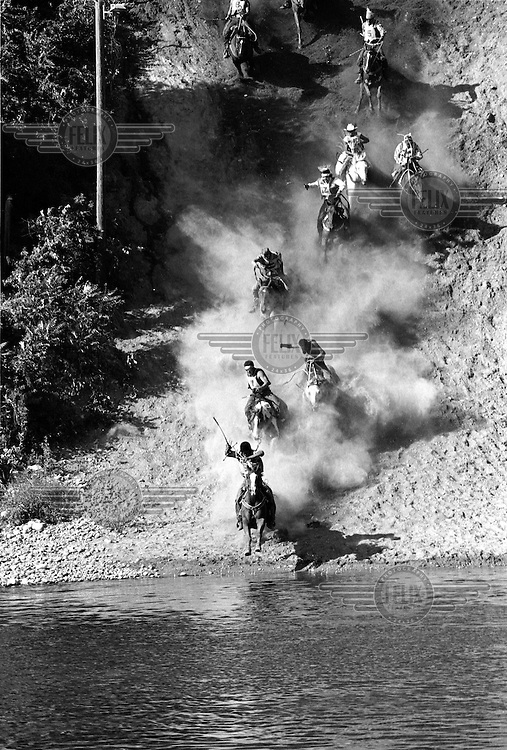 Tony Marchand's horse reaches the Okanogan River, at the bottom of Suicide Hill, in first place. He is eventually overtaken by Johnathan Abrahamson (second place), the overall Suicide Race winner. The Omak Suicide Race is part of the Omak Stampede, a rodeo which is held on the Colville Native American / Indian Reservation...
