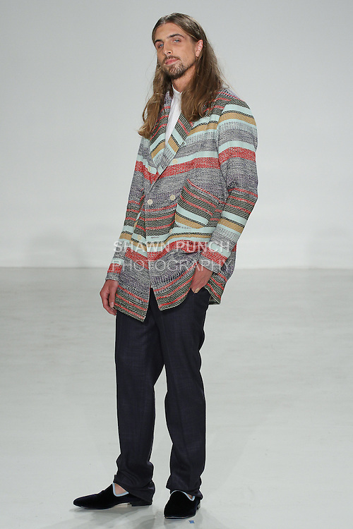 Model walks runway in a technicolor hobo coat, white linen popover, and cashmere/silk navy como trouser, from the Palmiers du Mal Spring Summer 2017 collection by Brandon Capps and Shane Fonner, at Skylight Clarkson Square on July 14 2016, during New York Fashion Week Men's Spring Summer 2017.