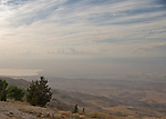 The view of the Biblical Promised Land from the top of Mount Nebo, Jordan.  The water to the left is the Dead Sea, while present-day Israel is directly ahead.  This is the closest the modern visitor can come to imagining Moses' sight of the Holy Land, as reported in the Bible.  Today a Christian church stands here, but across the ages, peoples of all religions have been able to worship here without persecution.  This was even true in as Christians were persecuted elsewhere in Ancient Rome, and continued though the Crusades and the Islamic caliphates, all the way to today. © Rick Collier