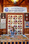 Old Bethpage, New York, USA. September 28, 2014. A member of the Long Island Quilters Society, L.I.G.R.A., sits at a display of traditional quilted rugs on a table and hung on the wall in the Exhibition Hall, at the 172nd Long Island Fair, a six-day fall county fair held late September and early October. A yearly event since 1842, the old-time festival is now held at a reconstructed fairground at Old Bethpage Village Restoration.
