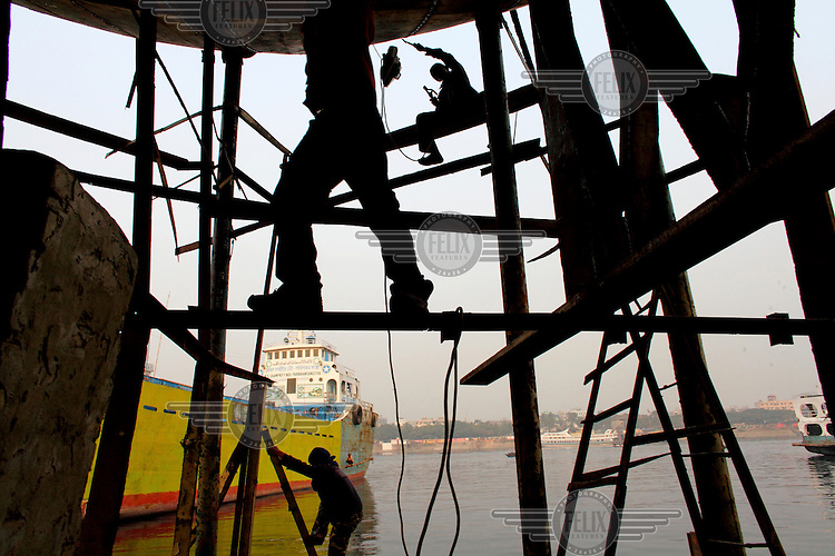 Labourers work on the construction of a ship at a ship building yard in Dhaka.