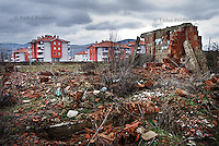 Ruins of one of the houses in Roma Mahala in southern Mitrovica that was destroyed in 1999. New apartment blocks in the background were built for Roma people as a part of the plan for their return.