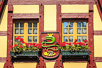 Germany, Bavaria, Middle Franconia, Rothenburg ob der Tauber: Gerlachschmiede (Old Forge), close-up of windows and the coat of arms with the crowned serpent, created by the legendary blacksmith Georg Gerlach himself | Deutschland, Bayern, Mittelfranken, Rothenburg ob der Tauber: Die Gerlachschmiede, Detail - Fenster und Wappen mit der gekroenten Schlange vom Schmied Georg Gerlach
