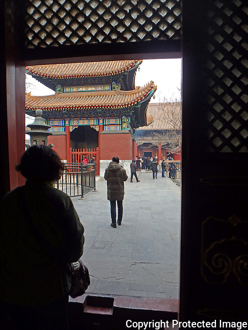 woman silhouetted at doorway of Buddhist temple looking across the courtyard toward another temple building a Lama Temple, Beijing