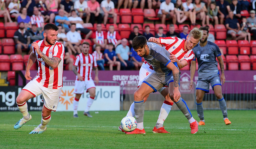 Lincoln City's Ellis Chapman vies for possession with Stoke City's Lasse Sorensen<br /> <br /> Photographer Chris Vaughan/CameraSport<br /> <br /> Football Pre-Season Friendly - Lincoln City v Stoke City - Wednesday July 24th 2019 - Sincil Bank - Lincoln<br /> <br /> World Copyright © 2019 CameraSport. All rights reserved. 43 Linden Ave. Countesthorpe. Leicester. England. LE8 5PG - Tel: +44 (0) 116 277 4147 - admin@camerasport.com - www.camerasport.com