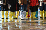 A group of tourists with boots and plastic bags to protect their shoes on flooded streets at St Mark's square during an acqua alta (high-water). The Acqua Alta, a convergence of high tides and a strong sirocco, reached 125 centimetres in Venice, on November 20, 2013.  <br /> <br /> &copy; Pierre Teyssot
