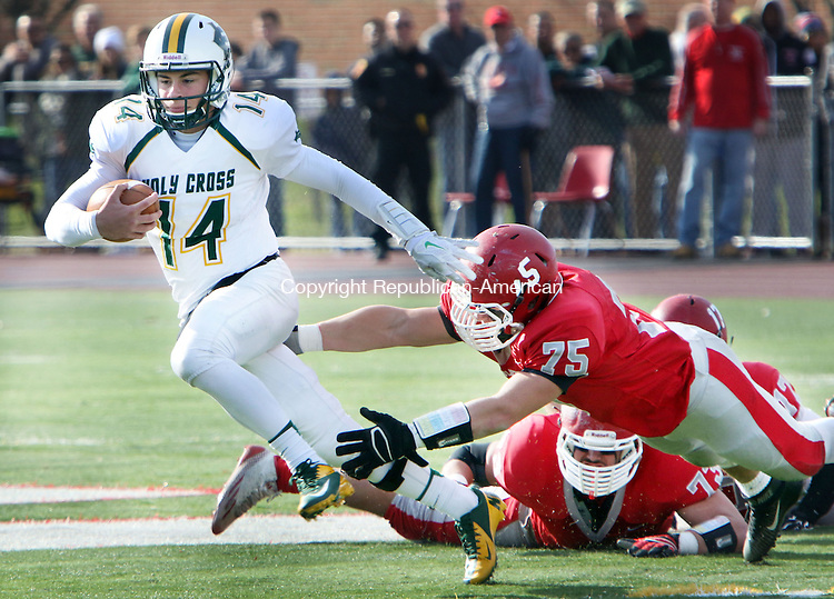 WOLCOTT CT. 26 November 2015-112615SV06-QB #14 Adam Razza of Holy Cross High keeps the ball for a 1st quarter run as #75 Robert Stoeckert of Wolcott High tries to grab him during football action in Wolcott Thursday.