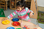 Education Preschool 3-4 year olds girl sorting colored plastic bears into matching color plates