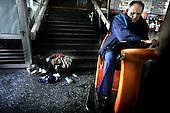 Warsaw 07.04.2008 Poland<br /> A homeless old women lie on ground at the Warsaw centre railway station while man, from cleaning service, clear the floor on his cleaning machine<br /> (Photo by Adam Lach / Napo Images for Newsweek Polska)<br /> <br /> Dworzec kolejowy, Warszawa Centralna. Bezdomna starsza kobieta lezy na ziemi podczas gdy czlowiek z serwisu porzadkowego czysci podloge<br /> (Fot Adam Lach / Napo Images dla Newsweek Polska)