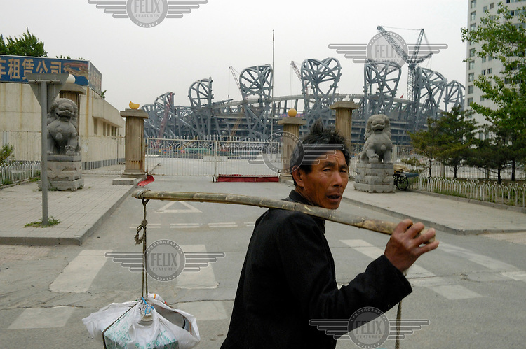 A labourer near the construction site of the 2008 Olympic stadium. The original 'bird's nest' design by architects Herzog & de Meuron was simplified by the Chinese once the bid for the Olympic games was successful.