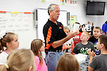 "Newell often delivers shaved ice from his stand to the classrooms at Leslie County High School and Mountain Elementary School on Thursday, Oct. 10, 2013 in Hyden, Ky. Newell has owned the Tropical Sno stand with his wife for almost 18 years. The stand, which is the only one of its kind in town, is right across the street from the high school and doubles as Newell's photography studio. ""If you've lived in Leslie County for more than two days, you know John Newell,"" said Leslie County resident Betty Lashon. Photo by Tessa Lighty"