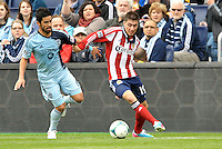Chivas Jorge Villafana (19) midfield USA watched by Paulo Nagamura  (6) midfield Sporting KC..Sporting Kansas City defeated Chivas USA 4-0 at Sporting Park, Kansas City, Kansas.