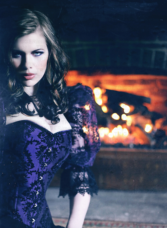 A lusty young blond woman in a lace corset stares intensely, sitting in front of a gothic fireplace, looking pale and dramatic
