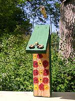 Kind, Kinder bauen Insekten-Hotel, Insektenhotel, Nisthilfe für Hymenopteren, Holzstück mit Bohrlöchern, Pflanzenstängel und leere Schneckengehäuse bieten Nistmöglichkeiten für solitäre Wildbienen und Wespen