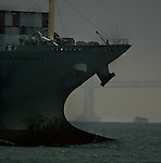 The bow of a supertanker leads the way out of the Bay Area under the Golden Gate Bridge, in San Francisco, California.