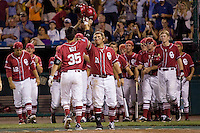 Oklahoma's Tyler Ogle celebrates hitting a HR with teammate Cody Reine in Game 10 of the NCAA Division One Men's College World Series on June 24th, 2010 at Johnny Rosenblatt Stadium in Omaha, Nebraska.  (Photo by Andrew Woolley / Four Seam Images)