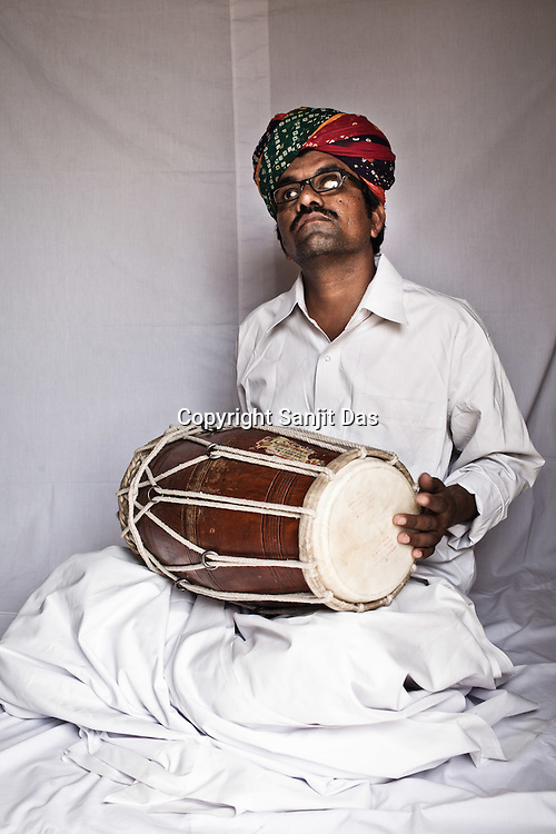 38-year-old Manganiyar artist and a Dholak player, Firoze Khan poses for a portrait inside his house in Hamira village of Jaiselmer district in Rajasthan, India. Photo: Sanjit Das/Panos