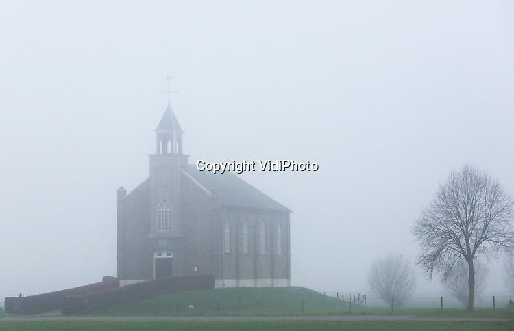 Foto: VidiPhoto<br /> <br /> HOMOET - Een kleine wereld woensdag in een groot deel van Nederland. Het midden, oosten en zuiden van ons land had woensdag te maken met een dichte tot zeer dichte mist, die voor veel overlast zorgde. Foto: Het kleine terpkerkje van Homoet in de mist.