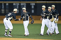 Joe Napolitano (12) of the Wake Forest Demon Deacons slaps hands with teammate Joey Rodriguez (8) after their win over the Delaware Blue Hens at Wake Forest Baseball Park on February 13, 2015 in Winston-Salem, North Carolina.  The Demon Deacons defeated the Blue Hens 3-2.  (Brian Westerholt/Four Seam Images)