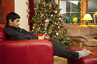 USA. Washington state. Fall City. ReStart Internet Addiction Recovery program at Heavensfield Retreat Center. Shlok is 22 years old and is a citizen from India. He seats in a red sofa and reads a letter during his Life Balance Plan Review session. He has dropped out of university because he was a highly addictive online video gamer on internet. ReStart is an unique intensive onsite program which offers to participants an opportunity to stay in a retreat center designed to promote insight and renewal, disconnect from digital distractions, and engage in coaching and mentoring while building a blue print for change. The three to six-month reStart program, the first of this kind in the United States, works to help men over 18, suffering from problematic internet, video game, social media and technology use by teaching positive and sustainable lifestyle change in a serene, rural environment surrounded by nature. 11.12.2014 © 2014 Didier Ruef