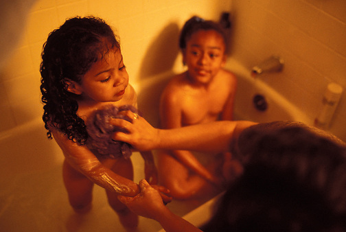"Pat bathes with her adoptive daughter, Bella. Pat first adopted Bella, left, and later Nina, center, so the two girls would not be separated. To Nina, Pat is her mother and role model. Nina calls her biological parents ""the donors."" (photo by Pico van Houtryve)"