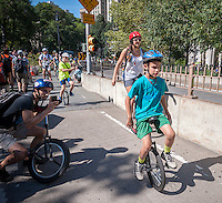 A young unicyclist rides across the Brooklyn Bridge during 13-mile trip to Coney Island on Friday, August 29, 2014 as part of the NYC Unicycle Festival. The convergence of unicyclists was the start of the 3-day Fifth Annual New York City Unicycle Festival which besides the ride, features performances, classes and just plain fun with events happening on Governor's Island. (© Richard B. Levine)