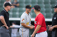 West Virginia Power manager Brian Esposito (36) smiles after exchanging lineups with Kannapolis Intimidators hitting coach Justin Jirschele (9) and umpires Justin Anderson (left) and Mike Carroll (right) at Kannapolis Intimidators Stadium on August 20, 2016 in Kannapolis, North Carolina.  The Intimidators defeated the Power 4-0.  (Brian Westerholt/Four Seam Images)