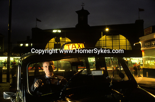 David Hines who is a London taxi driver as well as  an award winning author and playwright. 1990s. UK  In his cab outside Kings Cross train station.