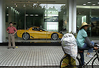 Corvette display in Guangzhou. A Chinese cyclist passes  a Corvette display window in Guangzhou, China. The Chinese government has been encouraging the purchase of automobiles; ownerships of vehicles including luxury models, have been on a steady rise..