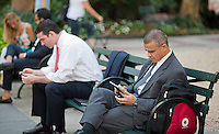 A reader uses his tablet computer in Bryant Park in New York on Tuesday, August 21, 2012 (© Richard B. Levine)