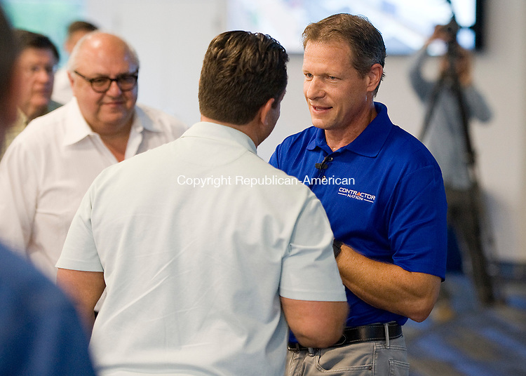 SEYMOUR, CT-0731117JS08-- Larry Janesky, right, owner of Connecticut Basement System, is congratulated by guests during the opening of the company's new 77,000 square-foot building in Seymour on Tuesday. The new building will be dedicated to education, entrepreneurship and economic success. <br /> Jim Shannon Republican-American