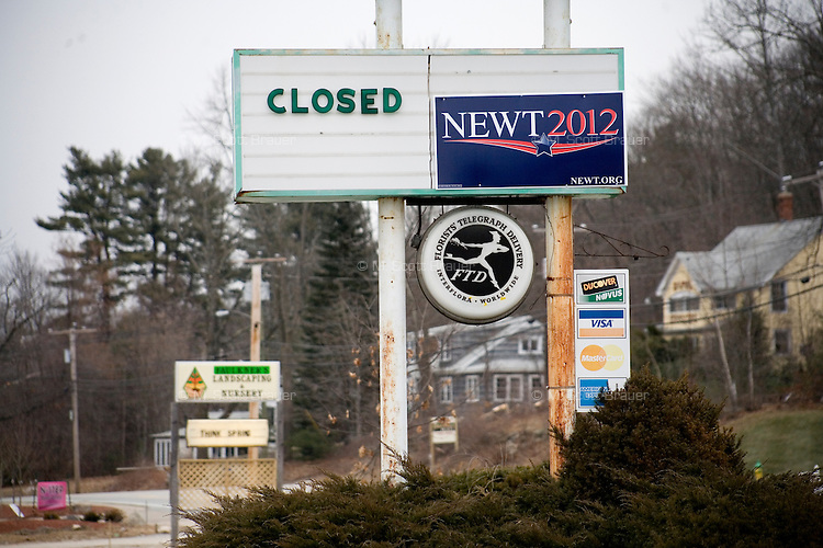 "A campaign sign for former Speaker of the House Newt Gingrich hangs next to a sign reading ""closed"" in Manchester, New Hampshire.  Gingrich is seeking the 2012 Republican nomination for president."