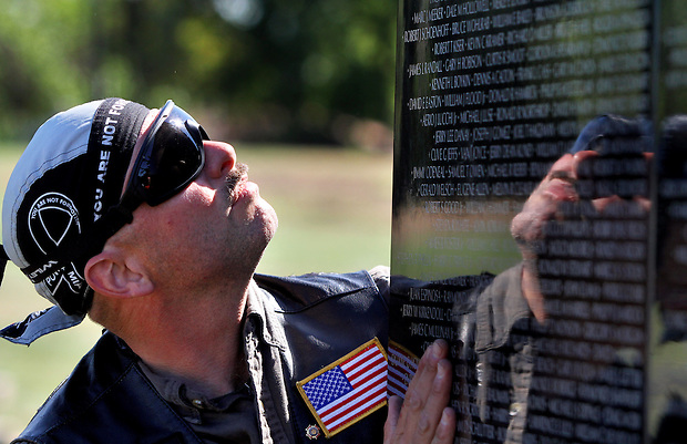 Vietnam-era veteran Jeff Kerr of Ankeny  looks at a panel bearing the names of those killed or missing in the Vietnam War during assembly of The Dignity Memorial Vietnam Experience Wednesday at Resthaven Cemetery in West Des Moines.  The display, a traveling, three-quarter-scale replica of the Vietnam Veterans Memorial in Washington, D.C., will be open to school children on Thursday and to the public at  from Friday to Sunday. The faux-granite replica is 240 feet long, eight feet high and contains the names of more than 58,000 Americans who died or are missing in Vietnam. More than 30,000 people are expected to see the display while it is in West Des Moines.  (Christopher Gannon/The Des Moines Register)