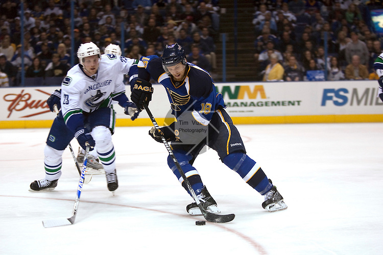 April 19 2009      Canucks player Alexander Edler (23, left) skates in on Blues player Jay McClement (18) as he brings the puck down the ice.   The St. Louis Blues hosted the Vancouver Canucks in the third playoff game between the two teams on Sunday April 19, 2009 at the Scottrade Center in downtown St. Louis, MO.  The Blues entered the game down 2-0 in the best of seven series.  ..            *******EDITORIAL USE ONLY*******