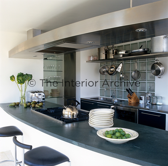 A black granite work surface has an integral hob with a stainless steel extractor and also serves as a breakfast bar