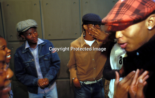 dipptee00049 .Teenagers well dressed partying in a club in Johannesburg, South Africa.  Boys standing against a wall. Hats..©Per-Anders Pettersson/iAfrika Photos