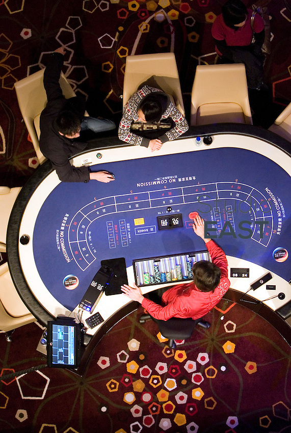 Gamblers play Baccarat in City of dreams casino, in Macao, China, on December 17, 2009. Photo by Lucas Schifres/Pictobank