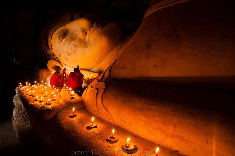 Two monks worshipping at the 18m long reclining Buddha in Bagan, Myanmar