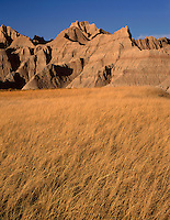SDBD_043 - USA, South Dakota, Badlands National Park, North Unit, Autumn colored grasses beneath banded, eroded sedimentary formations, near Norbeck Pass.