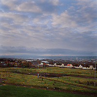 Wasteland looking down from north Belfast over the city. Flag poles are seen painted in red, white and blue, the colours of the British Union Jack flag. This is a traditional method of marking territory in Protestant estates loyal to the United Kingdom.