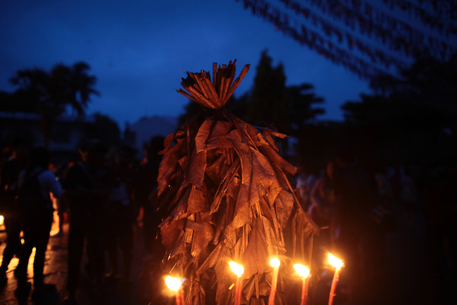 "A man prays before a set of votive candles during the annual Taong Putik,  or ""mud people,"" festival in Bibiclat, on Luzon island, Philippines. The festival honors St. John the Baptist, and devotees smear themselves with mud and dress in cloaks made from banana leaves and vines, which symbolize the animal skins the saint wore in the Bible.  June 24, 2011."