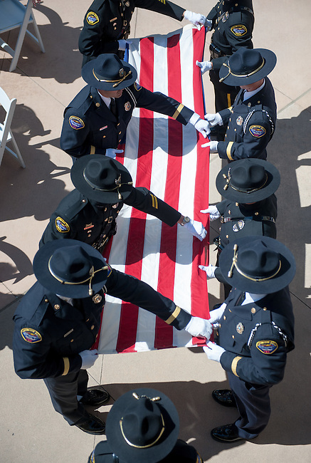 An honor guard comprised of Huntington Beach police and firefighters unfurls the special World Trace Center flag to be flown during the 9/11 ceremony.<br /> <br /> ///ADDITIONAL INFORMATION: hb.0915.memorial – 9/11/16 – MICHAEL KITADA, ORANGE COUNTY REGISTER - _DSC8579.jpg - <br /> Summary: The Huntington Beach Police Officers' Foundation's 9-11 Memorial Committee unveils a $200,000 monument including steel from the toppled World Trade Center, at City Hall. The event will include music, a flyover, New York police and others with connections to the 9-11 rescue and victims of the tragedy.
